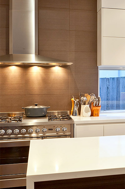 VMDesign Warm porcelain tiled splash back and modern range hood